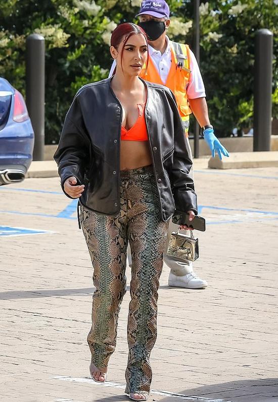 Kim Kardashian sành điệu ra phố hôm 28/6 với mái mới nhuộm đỏ, quần họa tiết da rắn Gucci, áo khoác da và bra màu cam nổi bật.