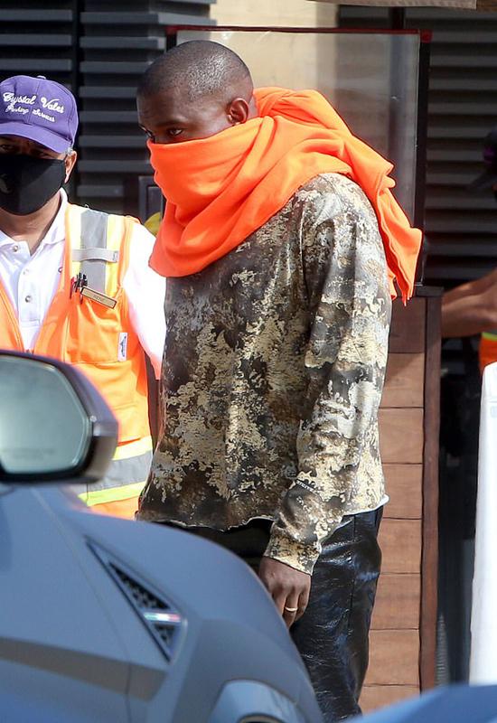 Trái ngược với vợ, rapper Kanye West quấn chiếc khăn to hở mỗi hai con mắt.