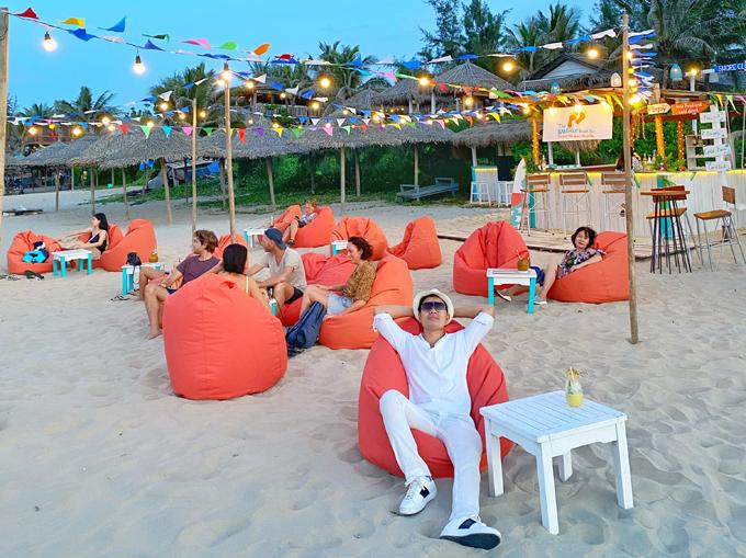 Anh thư thái ngả lưng trên ghế lười khi ghé thăm một quán cà phê bãi biển thiết kế đơn giản nhưng ấn tượng.