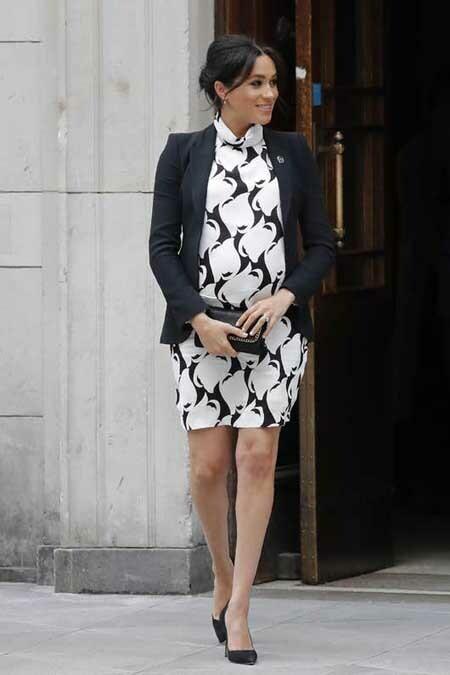 Meghan mặc váy ôm kết hợp áo vest, đi giày cao gót khi mang thai 7 tháng. Ảnh: AFP.