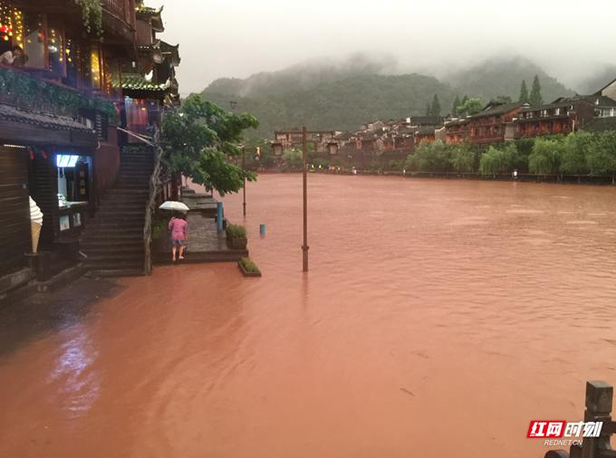 Nước sông Đà Giang dâng cao, nhấn chìm những con đường lát gạch bên bờ, gây khó khăn cho việc đi lại. Sở khí tượng thành phố Tương Tây đã nâng bức báo động đỏ, tiến hành di tản người dân và du khách đến nơi an toàn.