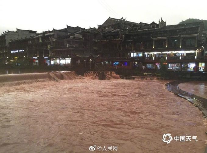 Nước dâng đến mặt cầu gỗ cong đoạn giữa sông Đà Giang. Ảnh Peoples Daily