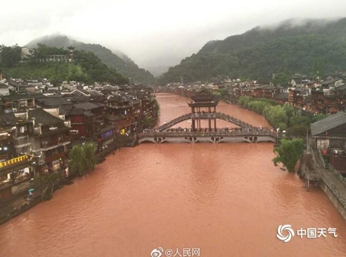 Gần cả tháng qua, Trung Quốc mưa lớn kéo dài khiến nhiều tỉnh thành như Trùng Khánh, Tứ Xuyên, Quý Châu, Hồ Bắc, Hồ Nam... bị ngập. Trong đó Phượng Hoàng cổ trấn thuộc tỉnh Hồ Nam là một trong những nơi chịu ảnh hưởng nặng bởi lũ. Đặc biệt từ 16h30 đến 20h ngày 29/6, lượng mưa ở Phượng Hoàng đạt mức 112,5 mm làm cả trấn cổ ngập trong nước lũ đục ngầu. Du khách, người dân dắt díu nhau thoát khỏi dòng nước chảy xiết. Ảnh Peoples Daily