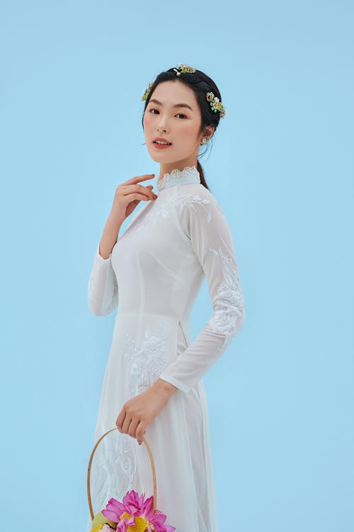 Áo dài trắng cách điệu với cổ đắp chút ren. Tà áo buông rủ, sắc trắng thuần khiết được điểm họa tiết thêu tay nơi ngực, mang nét duyên dáng.