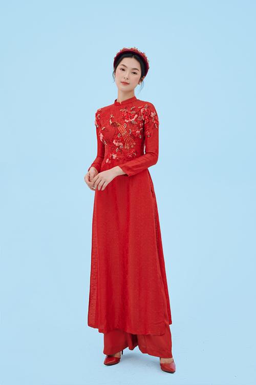 Áo dài đỏ thắm được xử lý sắc màu tinh tế cùng các mảng khối, bố cục hài hòa. Áo làm từ chất liệu cao cấp nên bền màu, bề mặt bóng mịn.