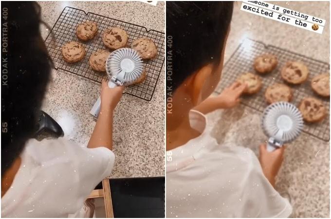 Con trai Tăng Thanh Hà dùng quạt cầm tay thổi bánh cho nhanh nguội.