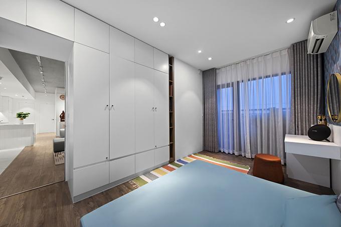 Phòng ngủ chính có nhiều tủ, kệ được tận dụng để ngăn với các khu vực chức năng, giúp tiết kiệm diện tích thay tường.