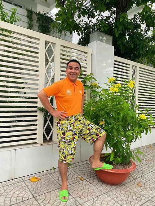 MC Quyền Linh gây cười khi đi dép tổ ong, mặc đồ sặc sỡ đọ sắc bên hoa.