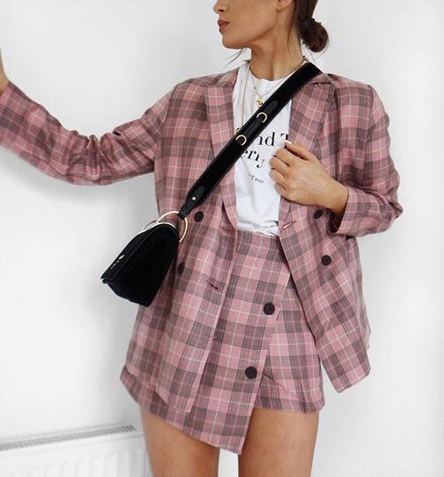 Áo blazer dáng rộng mix cùng chân váy ngắn với cấu trúc bất đối xứng nhưng lại mang lại tổng thể ưa nhìn và cá tính.