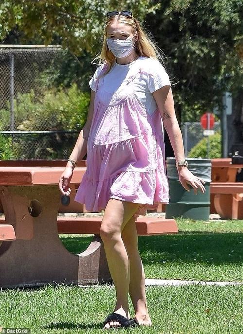 Sophie Turner mặc áo rộng, khéo léo che bụng bầu. Cô dùng khẩu trang để phòng chống dịch bệnh cho bản thân và bảo vệ sức khỏe cho đứa con trong bụng. Trong khi số đông người Mỹ phản đối đeo khẩu trang, ngôi sao phim Game of Thrones là một trong những nghệ sĩ lên tiếng ủng hộ việc sử dụng khẩu trang và hạn chế ra khỏi nhà trong giai đoạn đầu của Covid-19.