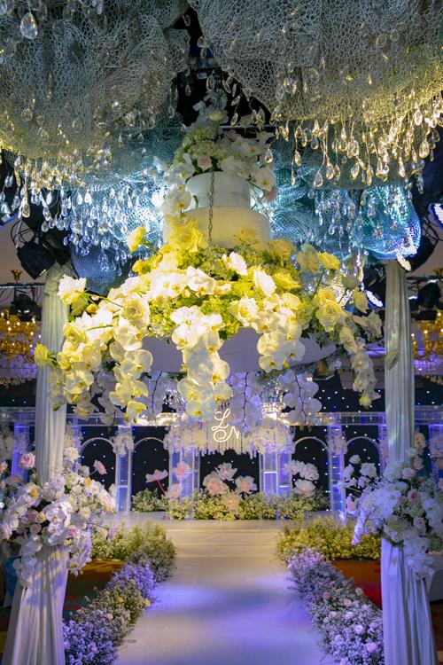 Bánh cưới của uyên ương được thả dần từ trần xuống dưới, tạo nên điểm nhấn trong chương trình tiệc.