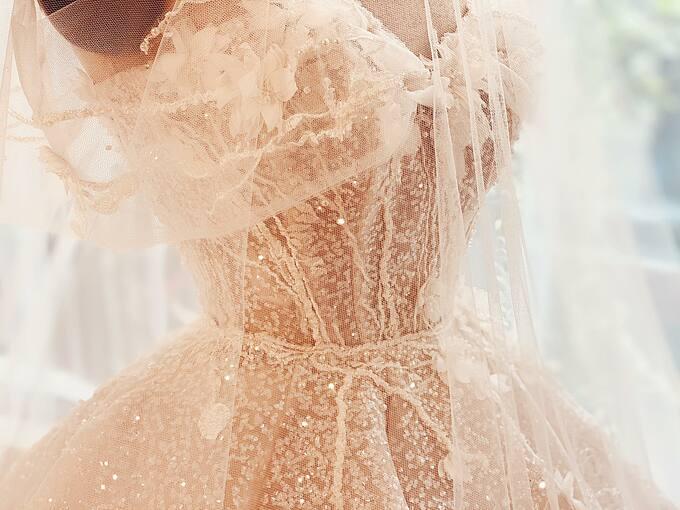 Những bông hoa mai trắng được cắt tỉa thủ công đính trên vai áo vào ôm theo đường cong cơ thể cũng chính là chi tiết cô dâu yêu thích nhất trên váy cưới của mình.