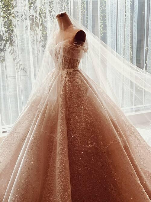 Phom váy dáng xòe nhẹ và mềm mại nhờ các đường xếp ly nơi tùng váy. Thiết kế có thể mặc thành hai kiểu tay dài và trễ vai khi thay đổi phần áo corset.