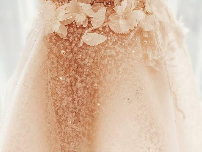 Váy được đính đá pha lê và có lớp vải dệt hạt đá nên dưới hiệu ứng của ánh sáng, chiếc váy như được thay đổi màu sắc liên tục.