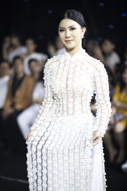 Áo dài trắng điểm khối hoa ren trải dài theo hàng dọc, giúp kéo dài chiều cao cơ thể một cách tự nhiên.