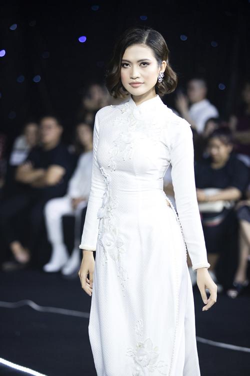 Minh Châu điểm trên tà áo dài trắng là những khối hoa hồng 3D, trải theo hình chữ S, là một phương pháp để tôn số đo của người diện.