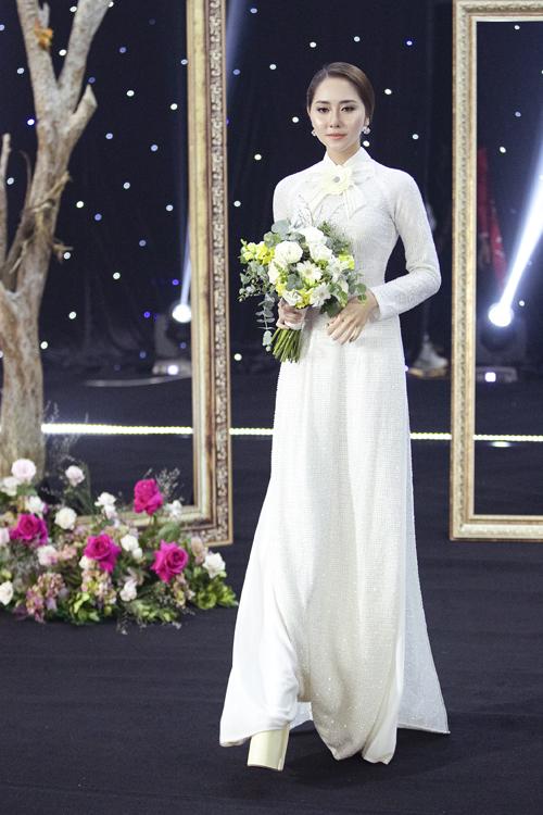 Điểm nhấn trên áo dài của Tường Vy là bông hoa đính ở cổ, mang nét thời trang phương Tây, tạo sự nữ tính cho người diện.