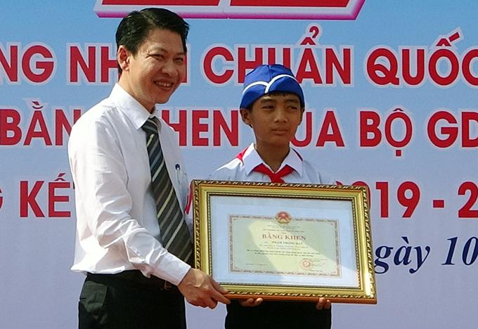 Đại diện Bộ GD&ĐT tặng bằng khen cho Đạt sáng 10/7. Ảnh: Hoàng Trường
