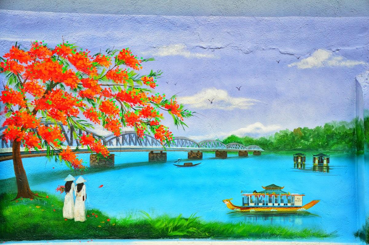 Cảnh cây phượng vĩ đỏ rực vào hè, phía xa là cầu Trường Tiền khắc họa vẻ đẹp xứ Hế. Cầu có 6 nhịp và 12 vài kết với nhau thành 6 cặp. Công trình hoàn thành năm 1899 dưới thời vua Thành Thái, dài khoảng hơn 400 m tính từ hai mố, lòng cầu rộng 6 m.