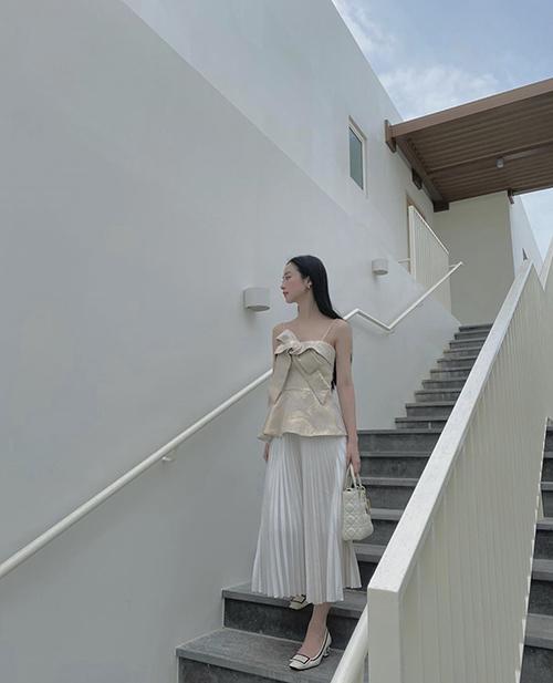 Chân váy mid là trang phục rất dễ mix đồ. Jun Vũ sử dụng áo hai dây tạo khối xinh xắn để phối cùng váy xếp ly.