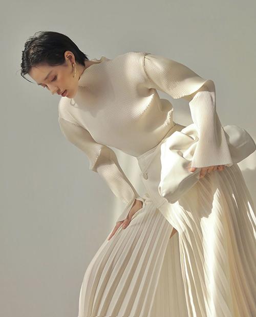 Khánh Linh khoe nét trang nhã và hiện đại với set đồ phối màu white on white. Áo xếp ly nhỏ được fashionista mix cùng chân váy xẻ hài hòa màu sắc.