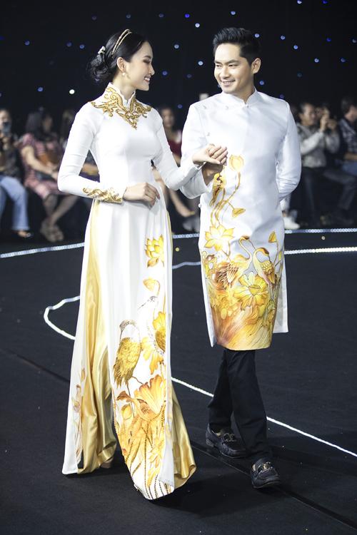 Áo dài mà diễn viên Minh Luân cùng người mẫu diện tái hiện bức tranh cặp chim hạc vui đùa trong đầm sen, ngụ ý về tình cảm quấn quýt, bền chặt của lứa đôi. Gam vàng trắng giúp bộ cánh sang trọng, tinh tế.