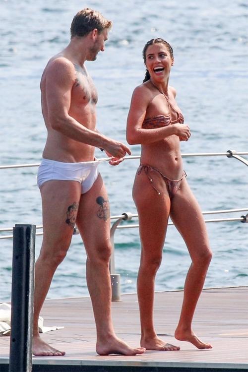 Cựu tiền đạo Arsenal và bạn gái cười đùa vui vẻ khi đi bộ trên du thuyền. Nicklas Bendtner mặc quần bơi màu trắng trông không khác gì quần lót trong khi bạn gái cũng mặc bikini kiệm vải.