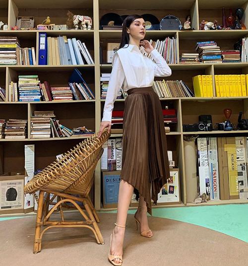 Nữ ca sĩ Mlee sử dụng chân váy tông nâu đậm cùng áo sơ mi biến tấu độc đáo để hoà cùng trào lưu ăn diện được ưa chuộng.
