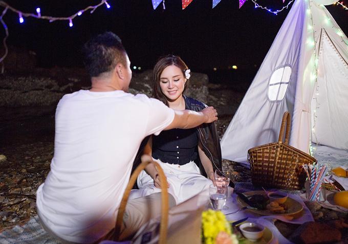 Họ cắm trại, ăn tối trên bãi biển lộng gió. Doanh nhân Lê Thiện ân cần choàng áo khoác để vợ khỏi bị lạnh.
