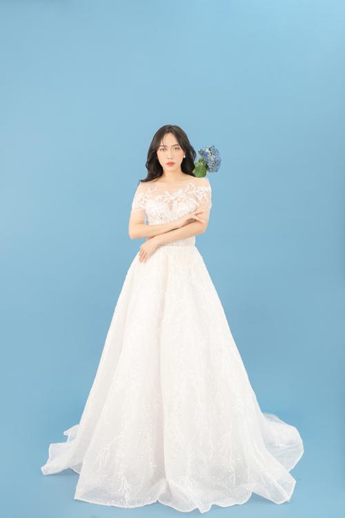 Bộ váy cưới trắng tinh khôi có phom dáng xòe, phần tay voan trễ xuyên thấu mang đến vẻ gợi cảm.
