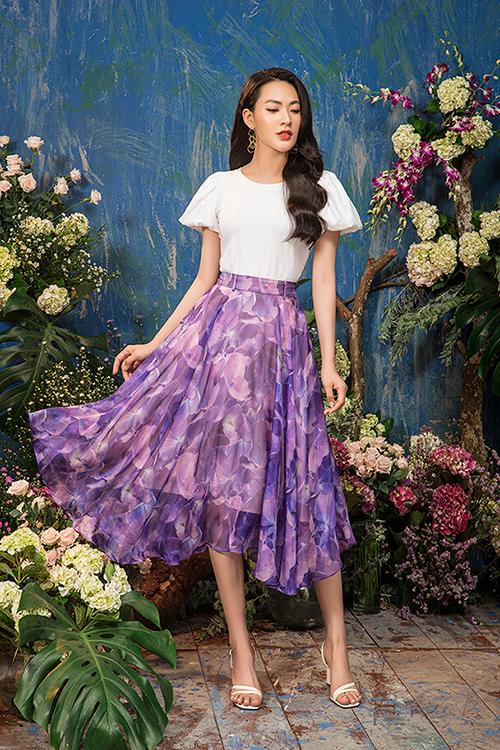 Cô chọn chân váy voan in họa tiết hoa to bản màu tím tử đinh hương kết hợp với áo trắng tay phồng điệu đà.