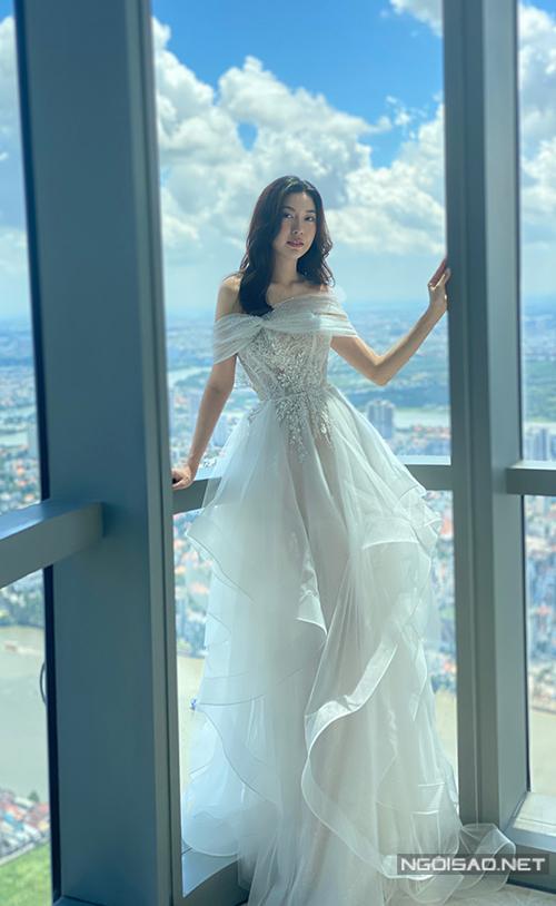 Theo đó, bộ váy cưới trễ vai đầu tiên của người đẹp được lấy ý tưởng từ đóa hoa hồng nở rộ trong vườn. Thiết kế tập trung vào nét dịu dàng cho người mặc nên được sử dụng chất liệu organza tơ tằm cao cấp. Các lớp vải của bộ váy này được sắp xếp khéo léo, tạo nên tầng váy lạ mắt, mang đến sự trẻ trung và tạo cảm giác nhẹ nhàng cho cô dâu khi di chuyển. Phần ngực áo cũng được điểm xuyết bởi hoa ren baby để tạo được sự lấp lánh nhất định.