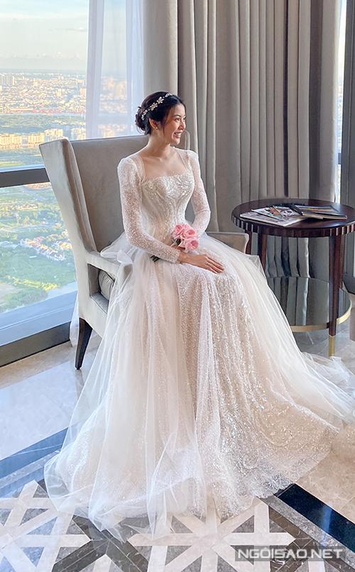 Khoác trên mình bộ váy cưới thứ 2 trong khung cảnh có view triệu đô, Á hậu Thúy Vân chuyển mình sang phong cách hoàng gia. Với mẫu váy cưới trễ vai tay dài, thiết kế đã giúp cô dâu mới khoe trọn bờ vai thon gọn của mình. Kết hợp chất liệu ren Pháp và vải voan ánh kim Hàn Quốc, cô dâu sẽ có được tổng thể hoàn mỹ của một cô nàng tiểu thư hoàn hảo, đầy thanh lịch.