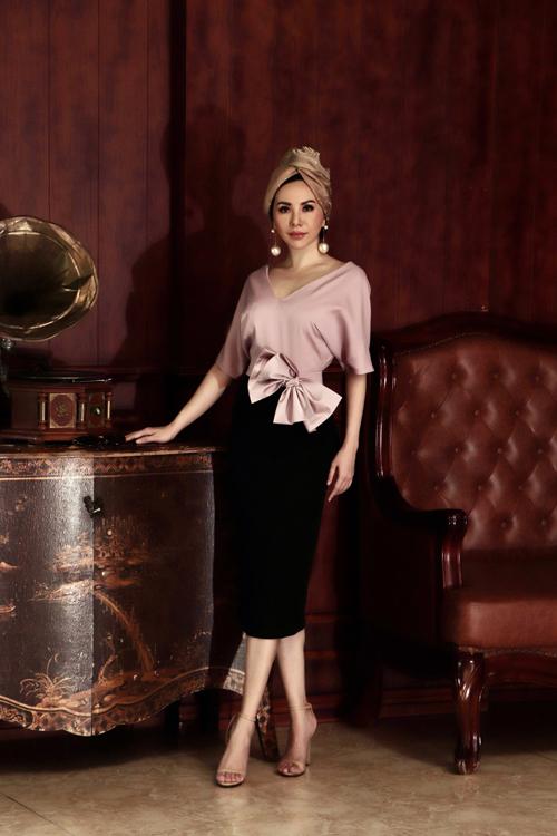 Set trang phục trên tông màu đơn sắc nhưng vẫn có thể giúp các nàng cuốn hút khi xuất hiện ở các buổi tiệc cocktail. Áo cổ V trang trí nơ bướm được phối hợp hài hòa cùng chân váy bút chì tôn đường cong.