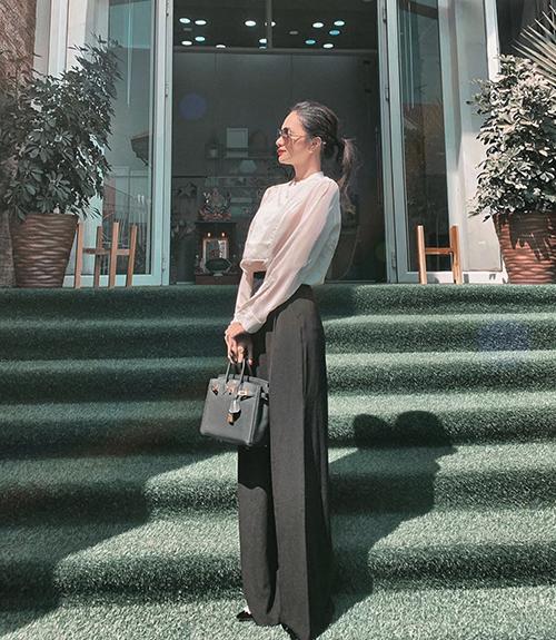 Hình ảnh nền nã của hoa hậu Hương Giang với lối mix đồ đen - trắng quen thuộc. Khi diện sơ mi ở mùa nóng, Hương Giang chọn thiết kế cổ trụ, vải mỏng manh tạo cảm giác thoáng mát.