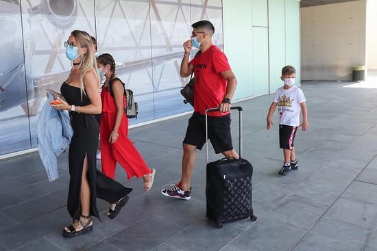 Luis Suarez (áo phông đỏ) và bà xã đi phía trước cùng các con đều đeo khẩu trang tới sân bay, chuẩn bị cho một kỳ nghỉ hè muộn. Suarez và Messi cùng 33 tuổi, hai bà vợ cũng thân thiết với nhau. Hai siêu sao đều có ba con nhưng Suarez có đủ nếp, tẻ còn Messi có ba cậu con trai.