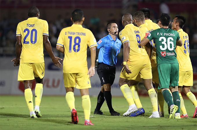 Cầu thủ Nam Định bao vây, phản đối trọng tài trong trận đấu với Nam Định. Ảnh: Đức Đồng.