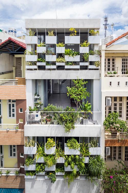 Vì thế, giải pháp chính cho kiến trúc của công trình là lắp đặt hệ thống chậu cây treo trên mặt tiền. Hệ thống vườn cây không chỉ đóng vai trò là màng chắn ánh nắng gay gắt vào buổi chiều mà còn hạn chế tầm nhìn của người ngoài vào trong nhà. Do đó, không gian sẽ yên tĩnh, riêng tư và mát mẻ hơn.