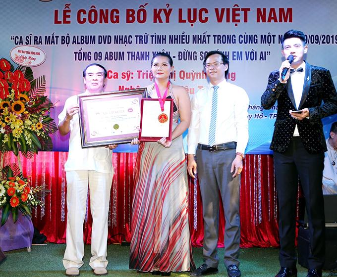 Ca sĩ Triệu Trang nhận giấy chứng nhận và kỷ niệm chương từ cựu đại sứ Ngô Quang Xuân (trái) và ông Hoàng Thái Tuấn Anh.