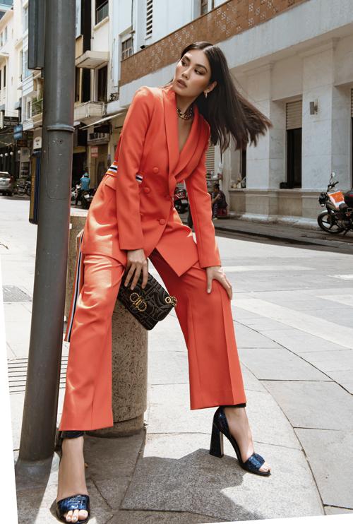 Bộ phụ kiện đồng điệu sắc đen được Thảo Nhi mix-match ăn ý cùng suit tông hồng cam đi kèm đai lưng kẻ sọc phá cách và trẻ trung.