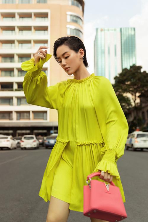 Khánh Linh sử dụng túi Louis Vuitton hồng cam để mix màu bắt mắt với váy xếp ly và trang trí bèo nhún độc đáo.