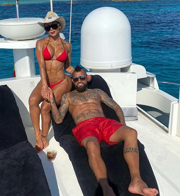 Tiền vệ cá tính người Chilê Arturo Vidal khoe hình xăm khi cởi trần, mặc quần đỏ đồng điệu với bộ bikini của bạn gái.