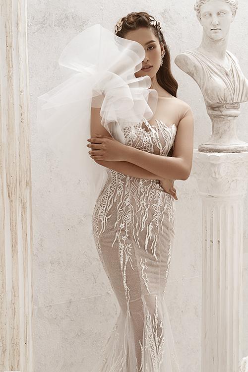 NTK đặt nặng yếu tố thẩm mỹ trong mọi tác phẩm, giúp váy cưới trở thành trang phục mãn nhãn, đáp ứng kỳ vọng về lễ phục cưới ngày đại hỷ của nàng dâu. Lớp vải lót phía trong nền ren tiệp màu da, giúp bộ cánh thêm quyến rũ.