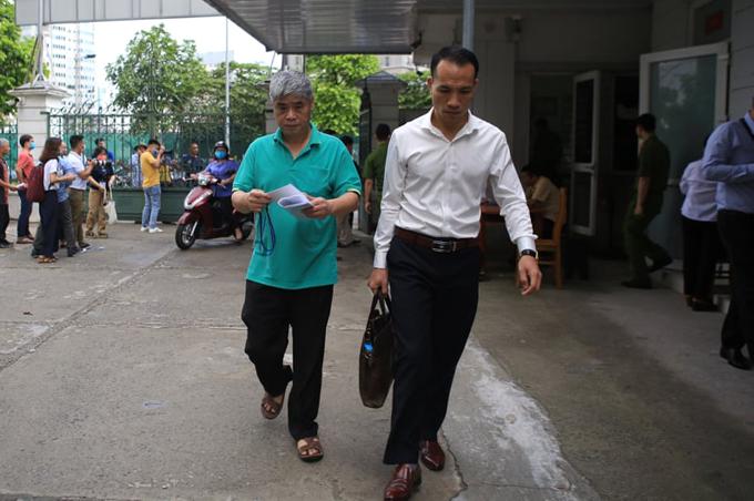 Bị cáo Doãn Quý Phiến (áo xanh) đến tòa cùng luật sư sáng 18/5.