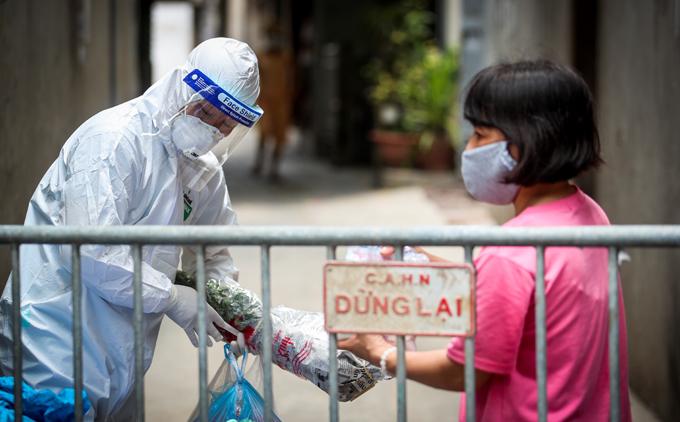 Ngõ 230 Mễ Trì Thượng được phong tỏa, nhân viên y tế kiểm soát người dân ra vào. Ảnh: Phạm Chiểu.