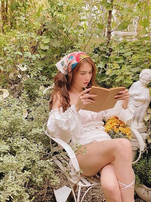 Ngọc Trinh diện set đồ bèo nhún màu trắng tinh khôi, khăn turban quấn đầu... khi ngồi đọc sách giữa khu vườn ngập sắc xanh.
