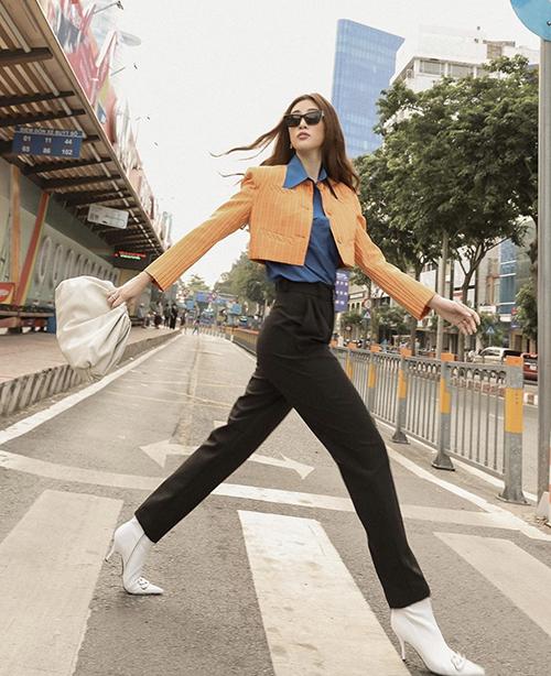 Jacket dáng lửng thiết kế trên tông màu nổi được mix ấn tượng cùng sơ mi và quần âu ống đứng. Khánh Vân chọn bộ phụ kiện tông trắng kem để hoàn thiện set đồ dạo phố.