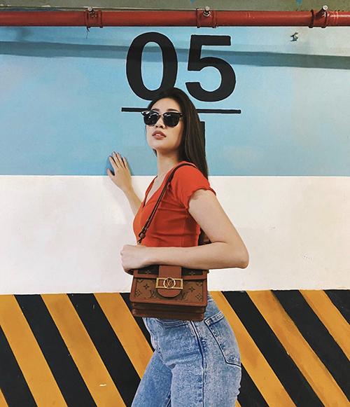 Diện áo thun tông đỏ cam cùng quần jeans dáng cơ bản, Khánh Vân chọn túi Louis Vuitton để mix đồ.