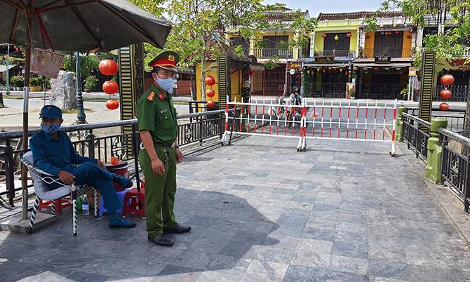 TP Hội An dựng hàng rào phong tỏa trên cầu An Hội đường ra vào khu phố nơi cư trú của bệnh nhân 428, sáng 30/7. Ảnh: Sơn Tủy.