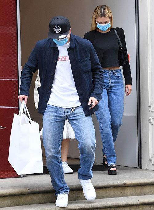 Brooklyn đeo khẩu trang, một tay cầm chìa khóa xe, một tay cầm túi đồ bước ra khỏi cửa hàng thời trang của mẹ ở thủ đô London, Anh. Phía sau cậu cả nhà Becks là vợ sắp cưới Nicola Peltz và cô em gái nhỏ Harper.